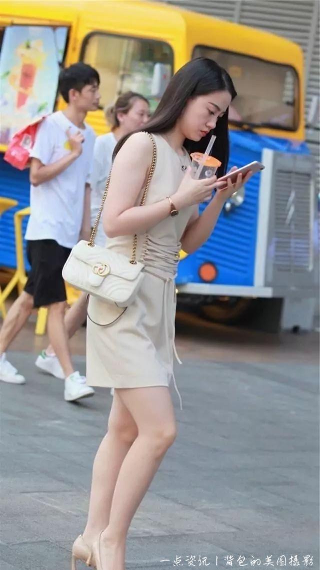 路人街拍,小姐姐短裙搭配高跟鞋,整体给人的感觉更俏丽时尚