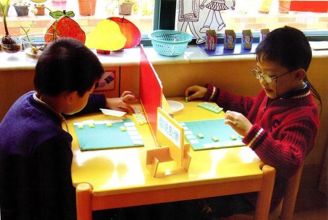 【4】朋友多多个人名片 材料:全班幼儿的大头照;夹子、剪刀等工具。 提示:1.鼓励幼儿自己制作名片,这既增加了游戏内容,同时也减轻了教师材料投放的压力。 2.教师可鼓励幼儿自带一些材料制作成个性化的名片。 玩法:1.幼儿剪下照片粘贴在夹子上,制作成个人名片。 2.幼儿可将名片用作作品展示及游戏规则的说明,如这是我的作品、我离开一会等。   【5】朋友多多你说我做 材料:底板(坐标式,如纵为数字、横为字母)与棋子各两套。 提示:1.