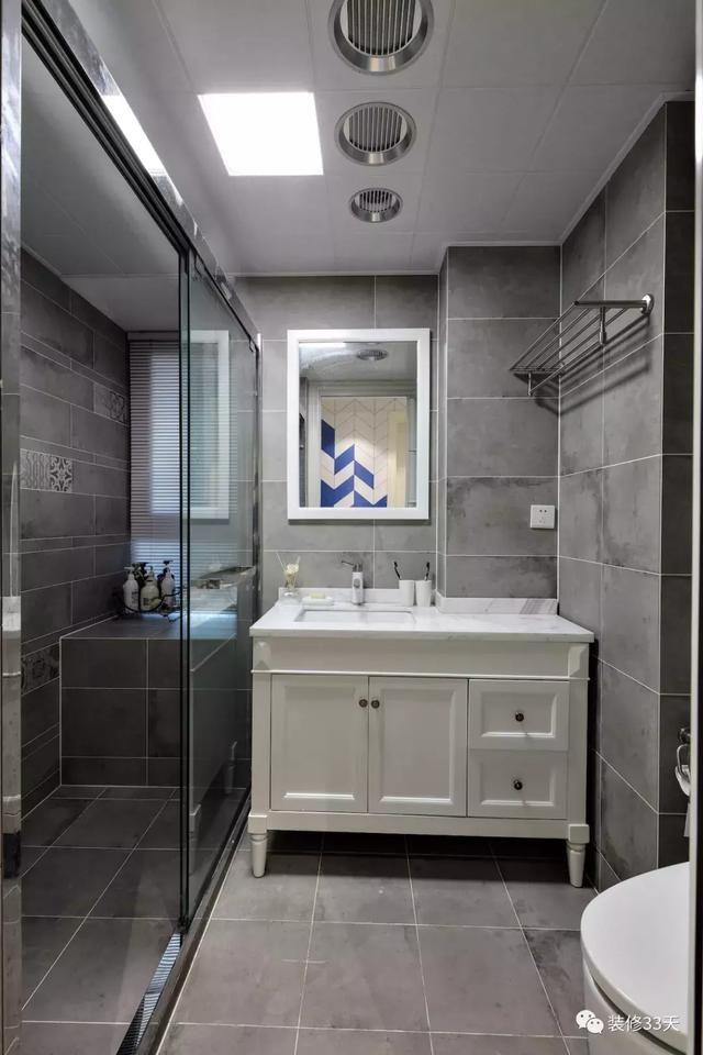 卫生间地面与墙面通铺灰色瓷砖,搭配白色定制台盆柜与墙镜,玻璃