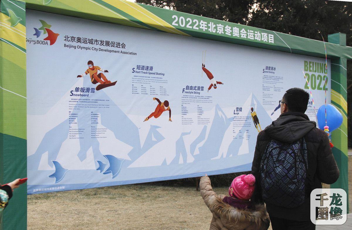 2018年2月16-20日,第三十五届龙潭庙会举行。图为驻足在展板前的一对父女。千龙网记者 袁帅摄 前来游逛庙会的章先生带着自己的小女儿驻足展板前,孩子看到关于2022年北京冬奥运动项目的展板指着问,爸爸,短道速滑和速度滑冰有什么区别啊?不都是穿上冰鞋在冰面上跑吗?这个......,我还是给你念念这上面怎么说的的!