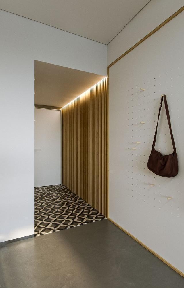 现如今,小户型以其较低的价位和高性价比开始得到更多人的青睐。这是一套面积为23平米公寓,设计师在最大化的满足户主的需求下,最大限度的提高空间利用率,采用智能和混拼方式,打造出一个宽敞实用的生活空间。 入户的墙面是一面白色插板,相较普通的装饰挂钩,牢固性更强,满足户主的基本需求。木栅栏墙面与地面花砖形成鲜明的对比。木板上方的集成LED照明为空间提供更加柔和的照明,不会打扰到其他人。  进门就是厨房区域,一字型橱柜布局局动线合理,对于一个人使用来说足够了。洗衣机嵌在橱柜的下方,充分节省了空间。白色吊柜的下方采
